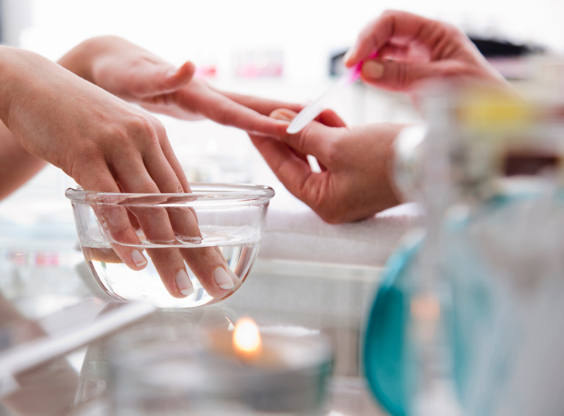 Woman soaks her fingernails in water while getting a manicure.